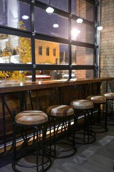 The restaurant features an original garage door that opens to allow an indoor-outdoor experience for guests seated at the walnut counter. The steel and glass door pairs with steel and wood barstools and an exposed brick wall for an ultra-industrial look.