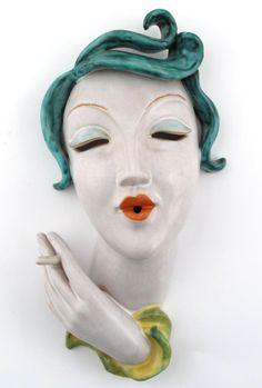 An Art Deco Goldscheider Pottery wall mask, modelled as a woman smoking a cigarette
