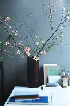 FLORAL ARRANGEMENT :: Simple flowered branches in a vase make this desk.