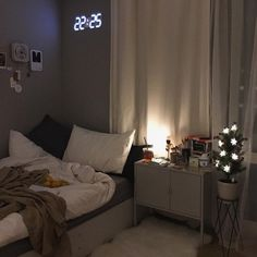 the room is small. curtains. lighting. furnished. cozy carpet on the floor. teen bedroom. gray walls