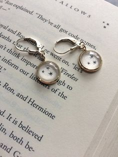 Sensitive skin rejoice! I now bring you these STERLING SILVER dangle earring! These earrings have the Harry Potter stars that are found in the corners of every page of the books. Select which Harry Potter book you want your stars taken from! Made of sterling silver, glass, and a book