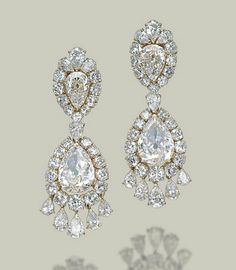 A MAGNIFICENT PAIR OF DIAMOND EAR PENDANTS, BY VAN CLEEF & ARPELS  Each top set with an inverted pear-shaped diamond, weighing approximately 2.44 and 2.30 carats, in a graduated brilliant-cut diamond surround, to the pear-shaped diamond pendant, weighing approximately 7.71 and 6.95 carats, in a similar surround and suspending a fringe of five pear-shaped diamonds, 6.2 cm, with French assay marks for gold, in grey suede Van Cleef & Arpels case Signed Van Cleef & Arpels, no. M39893