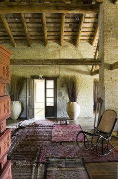 maybe I won't ever have a renovated mill in Italy, but I still love the layered rugs (tinged with pink), HUGE planters and cool painted brick walls.