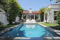 Backyard of a Spanish style home with a large pool in the backyard