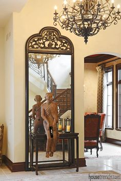 Foyer mirror reflects the statue of a monk at the base of a grand staircase.#housetrends