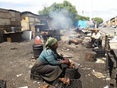Khayelitsha - Local woman sit on the side of the road in the sun preparing a local delicacy known as a 'smiley', (a sheep's head). Xhosa, Local Women, Smiley, South Africa, Sheep, Sun, Woman, City, People