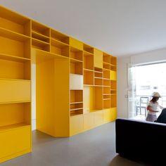 A yellow wall of storage divides this Portuguese apartment by architects Pedro Varela & Renata Pinho