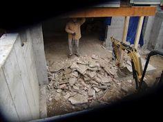 Mini excavator breaking up concrete