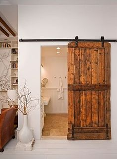Vintage Interior Design Inspiration. Absolutely IN LOVE with this old barn door hung on a rail.  This is a great statement piece that can be an alternative to pocket doors.