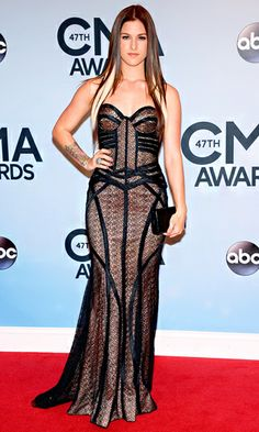 Cassadee Pope turns heads on the red carpet in a form-fitting, metallic-and-black, strapless Jovani gown. Pope pairs her dress with a black patent leather clutch by Lauren Merkin.