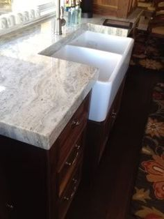 Fantasy Brown (soft) Quartzite polished. with dark cabinets and farmhouse sink. Visit globalgranite.com for your natural stone needs.