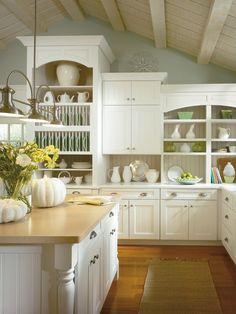 Clean and organized! Gorgeous kitchen! { this is one way to get more storage with a vaulted ceiling - stagger the cabinet height... }