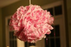 Take eight sheets of paper, line them up and fold them accordion style. wrap a rubber band in the middle then round the ends to make a softer flower look. separate the layers, and carefully pull each sheet out one at a time. Take any kind of ribbon or raffia and tuck it into your rubber band as the hanger.