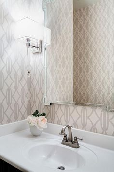Elegant powder room boasts walls clad in ivory and gray print wallpaper lined with a Mirror Image Home Key Corner Mirror illuminated by a long glass sconce over a vanity fitted with a satin nickel faucet.