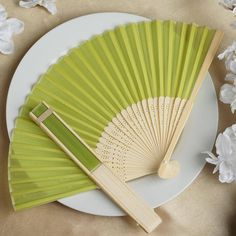 Asian Silk Folding Fans - Sage Green | eFavorMart / Add a classical Asian touch to your wedding, or a special event by presenting your esteemed guests with this special souvenir. Our stylish silk wedding hand fan is intricately handcrafted with a bamboo structure. The framing and spines are crafted from hand-picked bamboo and durably glued with a seamless cut piece of silk to fashion this immaculate magnum opus. Give these swish fans to your respected guests and let them create the lasting…