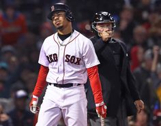 Boston, MA May 1, 2017: The Red Sox Mookie Betts grimaces after he was hit by a pitch from Orioles starter Dylan Bundy. Home plate umpire Greg Gibson directs him to firstbase. The Boston Red Sox hosted the Baltimore Orioles in a regular season MLB base ball game at Fenway Park. (Globe Staff Photo/Jim Davis)