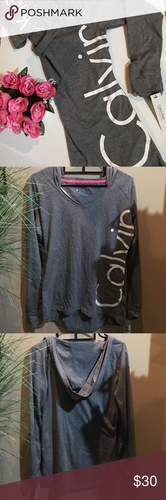 """Calvin Klein performance hoodie Long sleeve tee with hood. Calvin runs along side rib cage.  Klein runs down middle of hood. Cuffed sleeve. 25"""" long in front 27"""" long in back. Gray. Lightweight and stretchy. 60% cotton. 40% polyester. Calvin Klein Tops"""