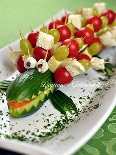 Ogórkowy krokodyl. Taki ogórkowy krokodyl jest idealną podstawką na koreczki. Bardzo ładnie prezentuje się na stole i zachwyca nie tylko dzieci. Koreczki można przyrządzić z dowolnymi dodatkami. Całość można przygotować spokojnie dzień wcześniej i przechować w lodówce.