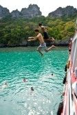 Travellers leap from the deck into the sea. Angthong National Marine Park, Suratthani province, Thailand. stock photography