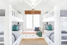 This kids' coastal bedroom from Wendy and Greg Blackband features shiplap walls, built-in bunk beds, nautical light fixtures, and whimsical elements such as a surfboard and lifeguard chair.