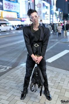 Kyosuke is an 18-year-old fashion student. Kyosuke is wearing a retro belted black jacket over a black top, Saint Laurent distressed jeans, and Hiro x George Cox patent buckle boots. Accessories include his House of Malakai chain mail veil, and a Prada backpack.