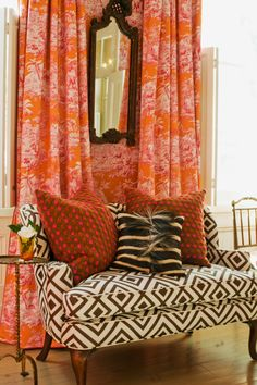 Pattern on pattern: orange toile walls and black and white graphic upholstery on the sofa