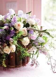 Designed by Paula Pryke. Arrangement of lavender sweet peas, roses, veronica and jasmine.