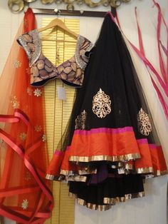 Black lehanga with pink, gold and orange border.  Orange dupatta with red and pink border and simple embroidery. Dark blue blouse with gold work. Langa oni/ half saree or ghagra.