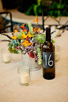 The dark bottle gives some needed contrast/inexpensive and can continue the 'chalk board' theme....would be nice to include some dk brown in florals...maybe brown eyed susans.....