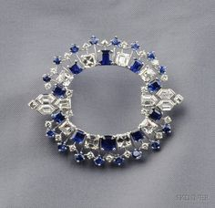Platinum, Sapphire, and Diamond Brooch, J.E. Caldwell, prong-set with ten step-cut and sixteen circular-cut sapphires, further set with eight square step-cut, two bullet, four hexagonal-cut and twenty-two circular-cut diamonds, approx. total wt. 8.00 cts., no. R8449, 2 1/4 x 1 3/4 in., signed J.E.C. & Co. Art Deco or Art Deco style.