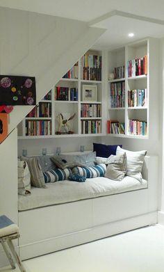 escalier bibliothèque et coin lecture 3 en 1, aménagé avec une banquette blanche, coussins et beaucoup de livres