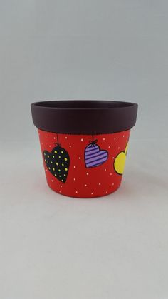 Vaso violeta tamanho grande em cerâmica tipo cachepô, pintado à mão. Vermelho na base e bordô na borda, pintura de varal de corações coloridos. Não há furos no fundo do vasinho. Pode ser usado como porta-treco, para colocar plantas ou uso apenas decorativo. Indicado apenas para uso inter...