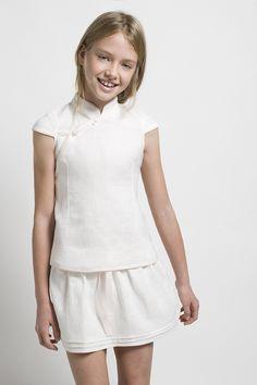 Total look blanco compuesto por una falda y una camiseta con cuello mao para niña.