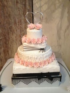 Black and pink wedding cake - My daughter and  I  made this cake for my sisters step daughters wedding. Two tiers of Red Velvet, White almond sour cream with raspberry filling, and a spice cake. And lots of sugar roses.