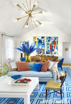 "To stay on budget, designer Gary McBournie initially resisted raising a Nantucket cottage's living room flat ceiling. ""But Bill found those strong abstract paintings by Silvio Cattani and fell in love,"" he says of his longtime partner. ""They were too big to hang in the room without raising the ceiling."" The rug is by Stark, and the vintage chandelier is made by Stilnovo."