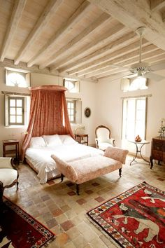 White painted ceiling beams, canopy bed and brilliant ethnic rugs. Eugenie-les-Bains