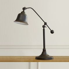 Featuring a bell shade and warm oil-rubbed bronze finish, this eye-catching lamp adds a mod touch to any table top. Set it in the den to light up your favorite reading nook, or add it to your office desk as a stylish touch to your workspace.