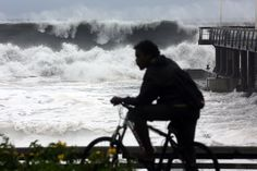 REUNION, Saint-Paul : A man rides along the sea on the northwestern coast of French Indian Ocean island of La Reunion on January 31, 2013 near Saint-Paul, as high waves hit the coastline, caused by the cyclone Felleng at 530 Km north of the island. AFP PHOTO / RICHARD BOUHET