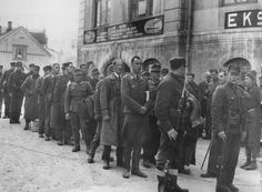 German prisoners of war under the supervision of Norwegian soldiers armed with Krag-Jørgensen rifles in the town of Harstad.