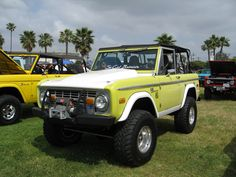 two tone Yellow Ford Bronco early off-road small SUV with white hood