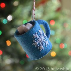 No Sew Hot Chocolate Ornament -Blue wool-blend craft felt, -Brown wool-blend craft felt, -White wool-blend craft felt, -White embroidery floss, size 5 -Cardboard TP tube pieces -Baker's twine -Craft Glue Felt Christmas Ornaments, Handmade Ornaments, Beaded Ornaments, Felt Ornaments Patterns, Pinecone Ornaments, Felt Christmas Decorations, Snowman Ornaments, Felt Crafts, Holiday Crafts