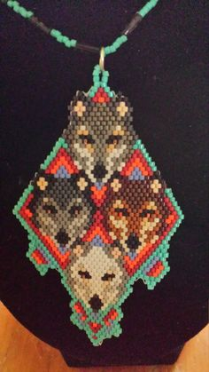A stunning depiction of four Wolf Brothers on Native American style background done in colors of orange red and turquoise and light purple. Indian Beadwork, Native Beadwork, Native American Patterns, Native American Beading, Seed Bead Patterns, Beading Patterns, Beaded Jewelry, Beaded Necklace, Beaded Animals