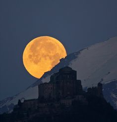 The moon peeking behind Alps and the Sacra di San Michele, northern Italy (National Geographic)