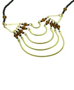 Five half-circles suspended from black and amber beads dangle and shimmer to give this piece subtle energy. This necklace is handmade in Kenya by skilled metal smiths working in brass.