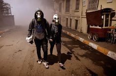 A couple wearing gas masks walk in a street between Taksim and Besiktas in Istanbul, Turkey, on June 4, 2013 during an anti-government demonstration.