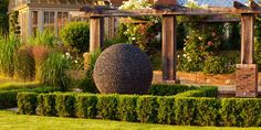 Dark Planet orb shaped sculpture in a colourful garden Garden Spheres, Garden Stones, Dark Planet, Paved Patio, Garden Photos, Backyard Projects, Colorful Garden, Modern Landscaping, Flower Show