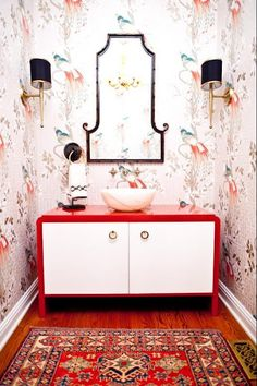 powder room. bird & greek key pattern on the wallpaper, mandarin-style bamboo-framed mirror, red & white console with marble sink and Persian carpet on hardwood floor. This style is only appropriate for a powder room and a home with no little children.