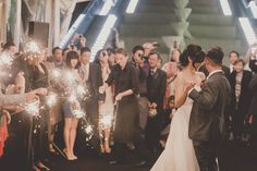 People in the background with sparklers shots Photography: Olive Studio - olivestudio.ca/ Photography:  Olive Studio  Read More: http://www.stylemepretty.com/canada-weddings/2014/04/07/modern-pink-malaparte-wedding-with-balloons/