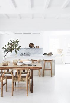 White is a classic kitchen colour palette for a reason, and this renovated 1920s Palm Beach holiday home makes the most of it. White kitchen cabinetry is paired with marble benchtops and splashback which add depth to this all-white home, and timber furniture warms the space up.