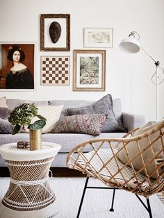 Eclectic Swedish living space with a gallery wall featuring a mounted chess board, a gray sofa, and an IKEA lamp
